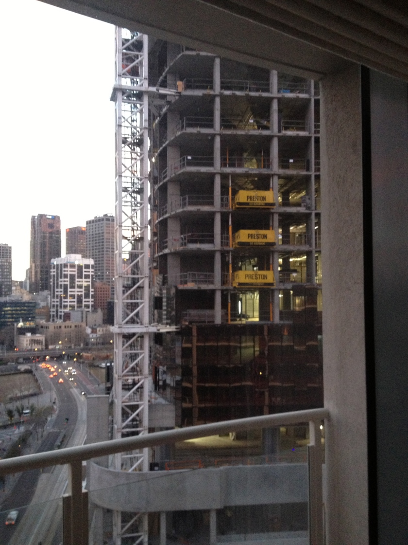 A view of a building under construction with tower crane attached