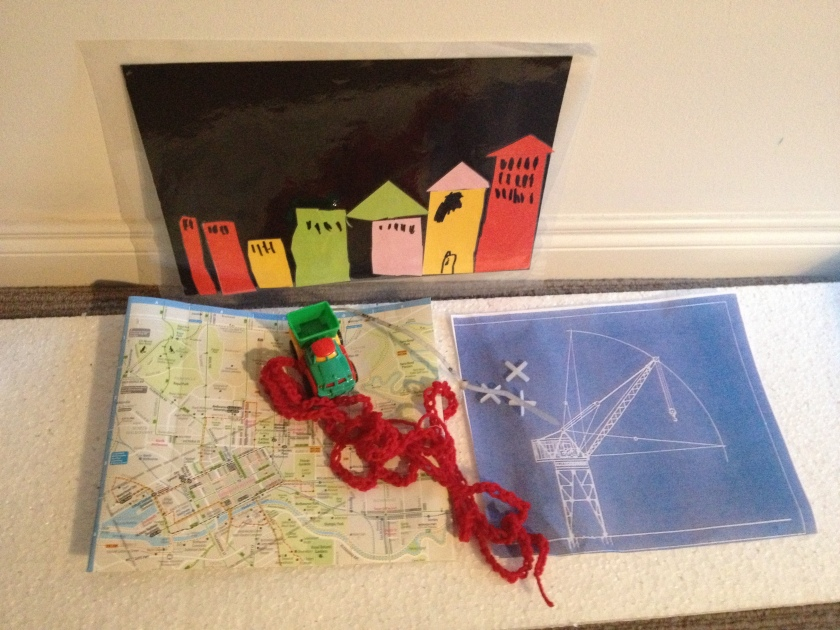 A map, blueprint, toy truck and child's artwork