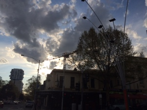 Cranes are silhouetted against a cloudy sky in suburban Carlton
